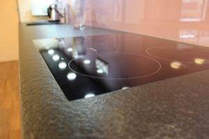 Kuchyně INFINI - DALIA vysoký lesk PLUS komb. SALSA lamino SPECIAL - ironwood tabák/ obklad sklo/ kámen NERO ASSOLUTO pat. (detail)