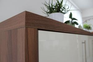 Kuchyně INFINI - NIKÉ Akrylát lesk (krémová bílá) / Lamino (ořech Dijon), obklad sklo, pracovní deska Umakart - detail