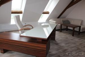 Stůl kombinace macassar / sklo magnolie, kancelářská židle s područkami. V pozadí pohovka Ponsel se stolkem z Lamina massacar